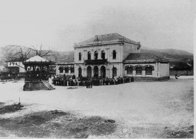 """Año 1894. Ayuntamiento y escuelas municipales. Frente a ellas el Kiosko de la música que data del año 1894. La primitiva es de 1755, fue derribada en 1887. Esta se adjudica en 1888 y se hace en 1889. Hubo una Fiesta del Arbol celebrada el 8 de febrero de 1899 (o 1894 como parece indicar la fotografía), fomentada por el maestro Calixto Díez para fomentar entre los niños el amor a la naturaleza. Esta zona de """"Deustua"""", perteneció a la anteiglesia de San Juan de Sondica (de la que luego se desmembró)."""